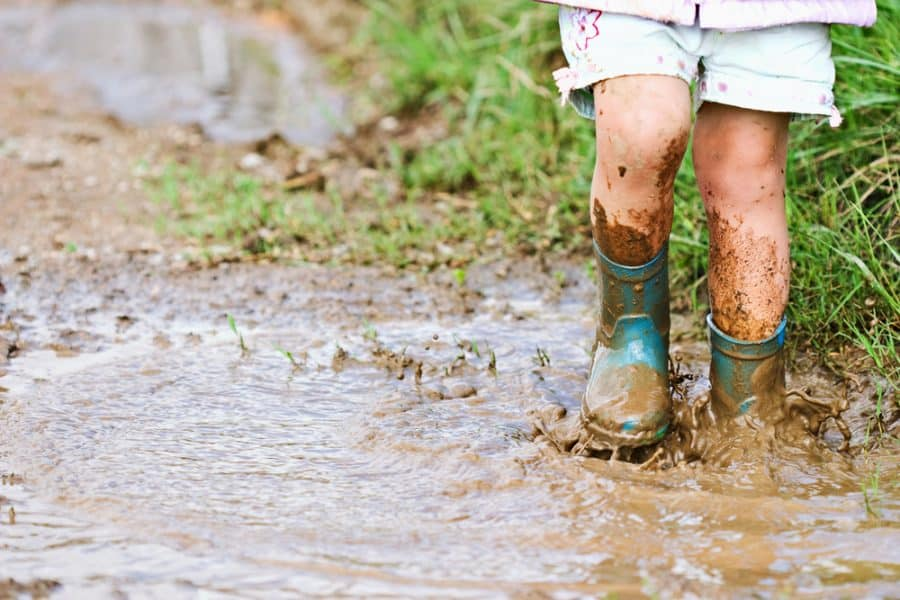Child splashing in mud puddle