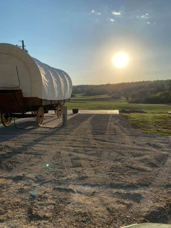 the camping rental, a covered wagon, as the sun sets over the hills of Kentucky