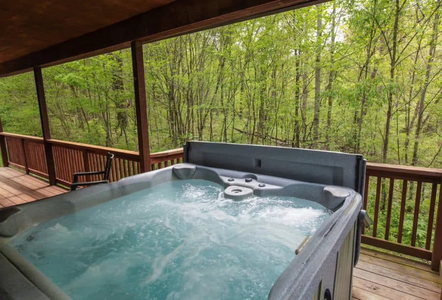 Hot tub on the deck overlooking the surrounding woods
