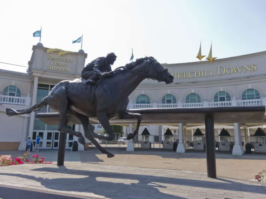 a horse and jockey statue in front of Louisville's Churchill Downs