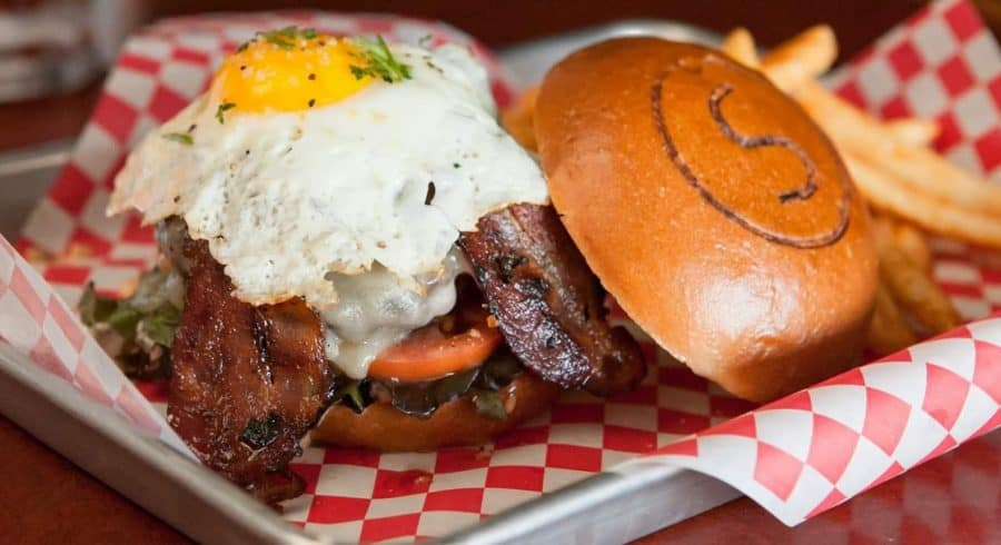 A burger topped with bacon and eggs, photo credit to Sammy's Craft Burgers