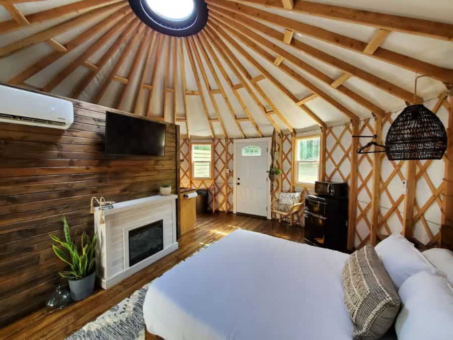 The inside view of a Yurt including a bed, fireplace, wooden beams, skylight