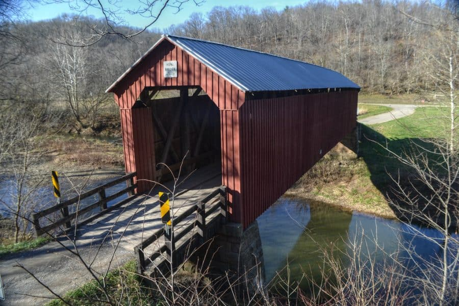 A red covered bridge over a creek